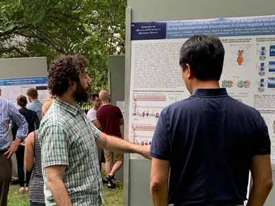 UVA Cell and Molecular Biology grad students viewing posters at a poster session on the UVA grounds.