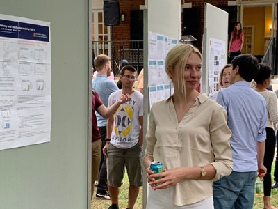 UVA Cell and Molecular Biology grad student standing proudly in front of her poster at poster session.